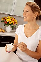 Woman In Kitchen Eating Yoghurt