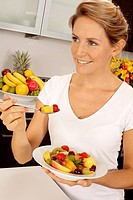 Woman In Kitchen Eating Fruit Salad