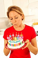 Girl With Birthday Cake Blowing Out Candles