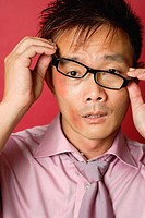 Businessman with bruised face, adjusting glasses