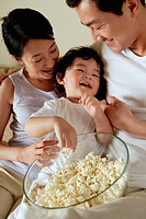 Parents with young son, eating from bowl of popcorn