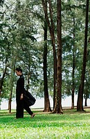 Young woman in traditional Chinese costume, walking amongst trees