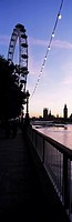 Looking along the Thames at dusk towards the London Eye, Big Ben and the Houses of Parliament, London, UK