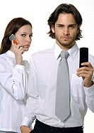 Portrait of a businessman holding a mobile phone with a businesswoman using a mobile phone beside him