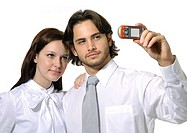 Close-up of a businessman and a businesswoman taking a picture of themselves with a mobile phone