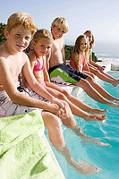 Kids sitting on edge of swimming pool