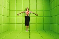 Woman laughing standing against wall of green padded cell (thumbnail)