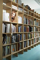 Woman peeping head through bookshelf (thumbnail)
