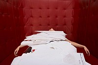 Businesswoman lying on table with red seating