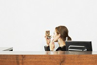Woman at a desk with a compact mirror