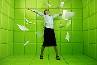 Woman throwing papers around green padded cell