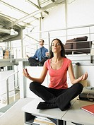 Young adults sitting on office desks in a yoga position (thumbnail)