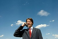 Man holding old phone against blue sky