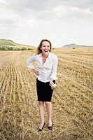Businesswoman fencing in a wheat field