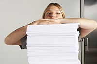 Young woman working from home with huge pile of paper (thumbnail)