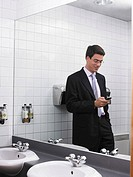 Man reflected in office washroom mirror using mobile phone (thumbnail)