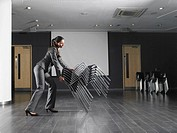Woman moving stack of chairs in empty presentation room