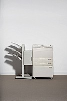 A photocopier against a white wall