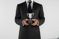 Man holding a small silver trophy