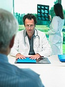 Two doctors discussing x-rays with mature patient