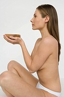 Young nude woman holding a bowl