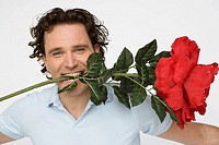 Man holding oversized flower between his teeth