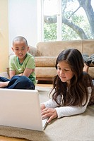 Siblings using a laptop in living room