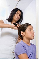Mother brushing her daughter's hair