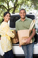 Couple unloading groceries out of car