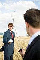Businessmen fencing in wheat field