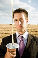 Businessman fencing in wheat field