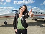 Woman giving thumbs up beside private jet