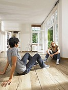 Two friends seated on floor of empty house