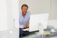 Man at computer smiling with reflections