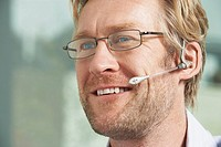 Close-Up portrait of Businessman using telephone headset / ear piece