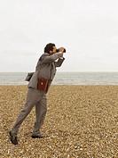 Businessman with Binoculars at Beach