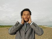 Businessman Covering Ears on Beach