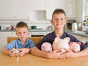 Young Boy Frowning beside Boy With More Piggy banks