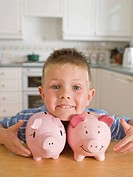 Young Boy Smiling With Two Piggy Banks