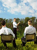 Group of businesspeople sitting on chairs in field