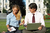 Businessman and businesswoman sitting in field working together