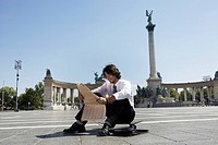 Businessman reading newspaper in Hero Square