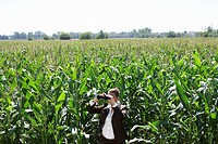 Businesswoman with binoculars in corn field