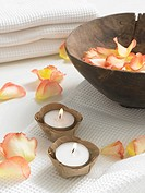 Rose petals in a wooden bowl and small candles on a piqué towel