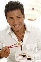 Asian man is eating sushi with chopsticks