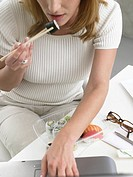 Woman is eating sushi at the desk