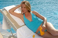 Woman with sun lotion at the swimming pool