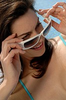 Woman with sunglasses next to the swimming pool