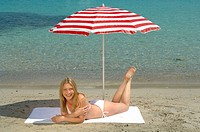 Woman lying on the beach under a sunshade