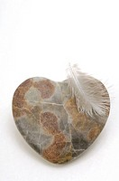 Heartshape stone and a white feather